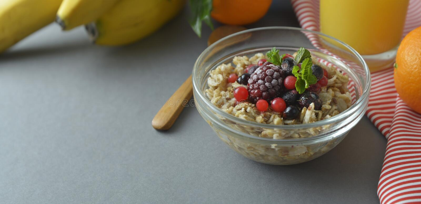 Healthy breakfast in a bowl with oatmeals, frozen berries, fresh strawberries, mint. Oat porridge with fruits. Banner stock image