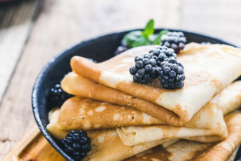 Homemade crepes, fresh summer blackberries powdered sugar. Healthy breakfast or brunch, favorite morning meal. Homemade crepes, fresh summer blackberry berries royalty free stock photography