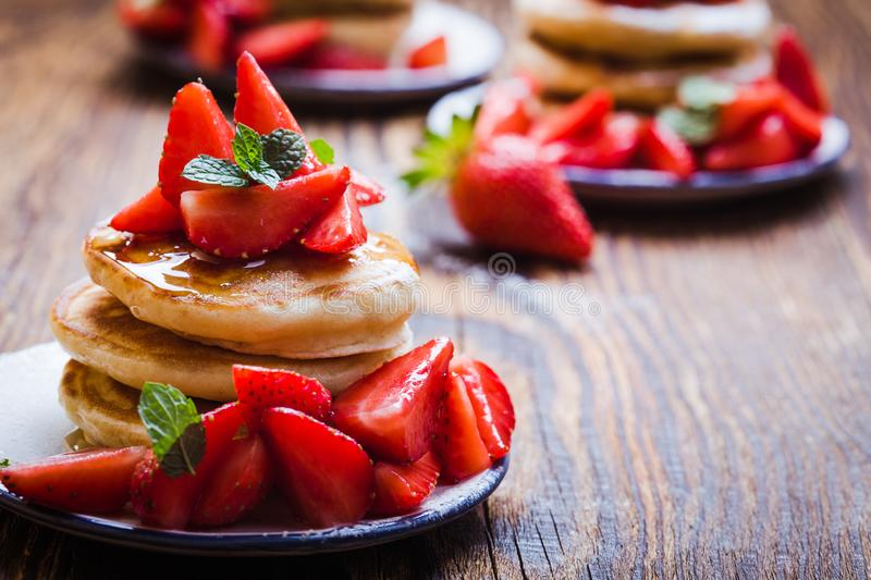 Breakfast or brunch, pancakes with fresh summer strawberries, powdered sugar, honey royalty free stock photo