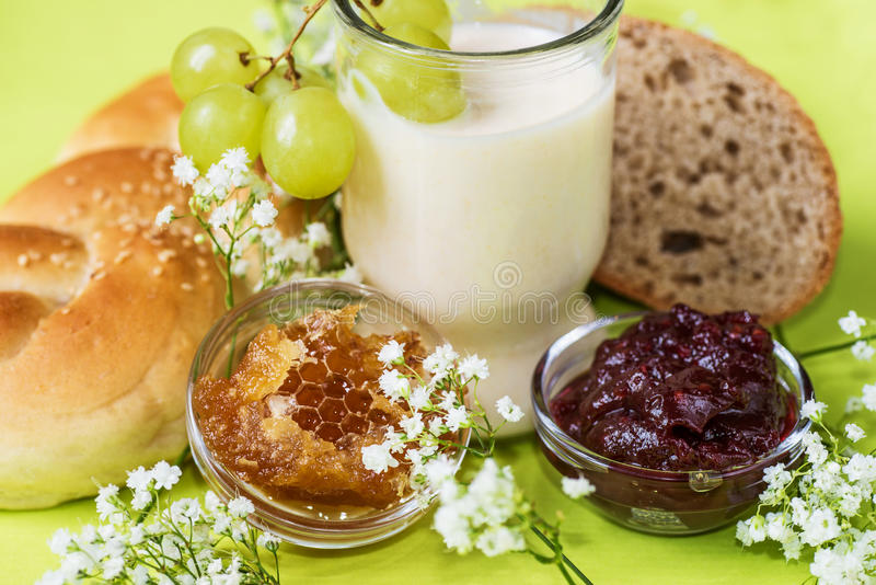 Healthy breakfast with bun, bread, honey, jam, glass of fermented milk and tiny flowers stock photos