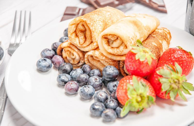 Healthy breakfast, coffee and homemade pancakes with fresh berries and banana stock photography