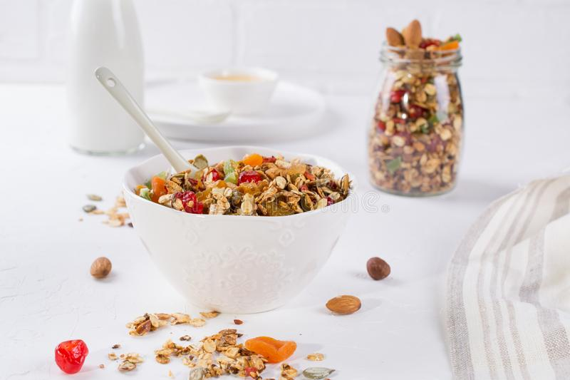 Healthy breakfast concept. Baked granola in white ceramic bowl and glass jar. On the kitchen table royalty free stock images