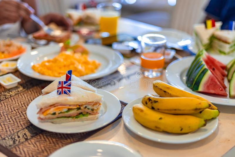 Healthy Breakfast Concept. Club Sandwich presented with English Flag on top along with fruits and juice at breakfast table stock photography