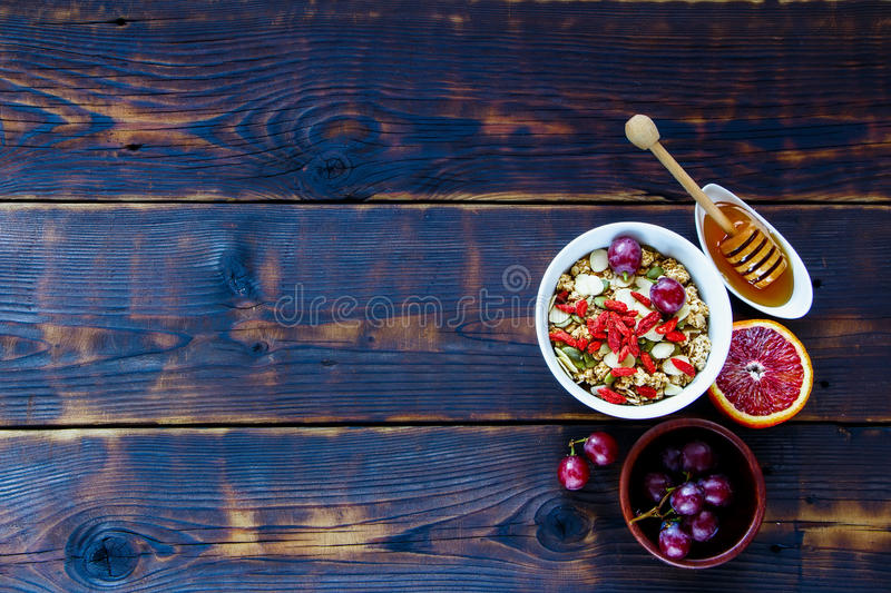 Healthy breakfast concept. Oatmeal, granola in bowl, dried berries, seeds, honey, bloody orange, grapes over dark wooden background, top view. Clean eating stock photography