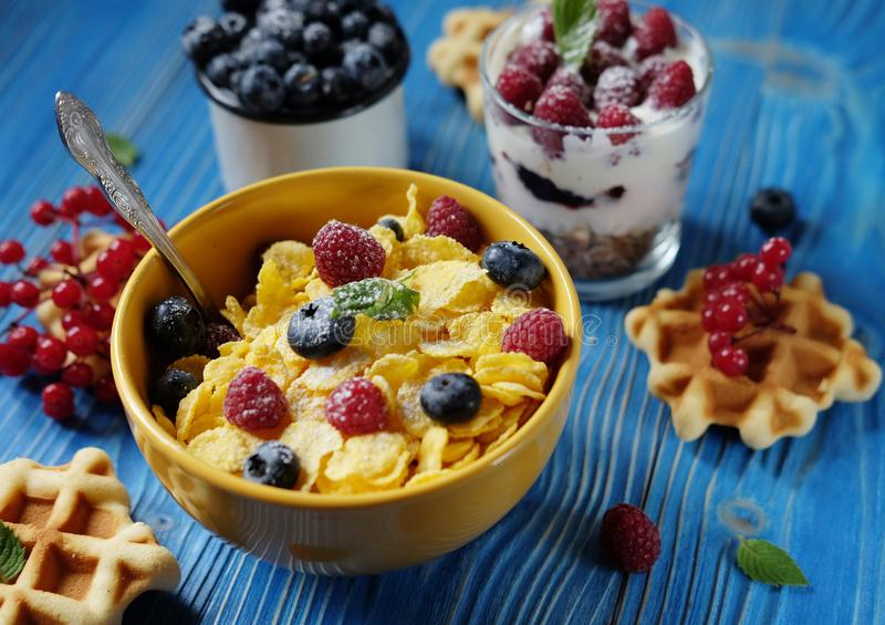 Healthy breakfast with corn flakes, berries, waffle and milk on blue background. Close up. Healthy breakfast with corn flakes, berries, waffle and milk on blue stock photo