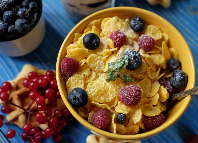 Healthy breakfast with corn flakes, berries, waffle and milk on blue background. Close up stock images