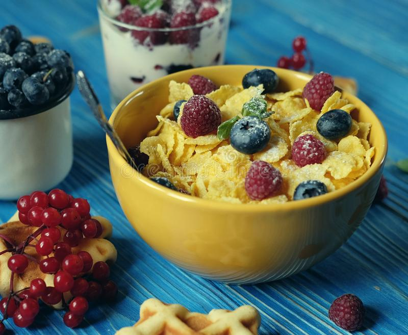 Healthy breakfast with corn flakes, berries, waffle and milk on blue background. Close up royalty free stock image