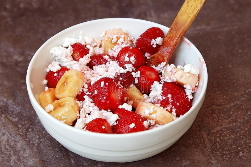 Healthy breakfast, cottage cheese with fruit strawberry and banana with wooden spoon. Organic natural diet concept. stock photography