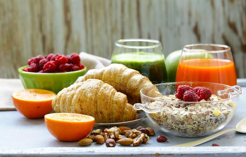 A healthy breakfast with croissants, fresh juice,. Nuts and raspberries royalty free stock image