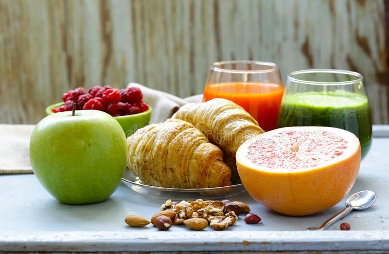 A healthy breakfast with croissants, fresh juice. Nuts and raspberries royalty free stock photo