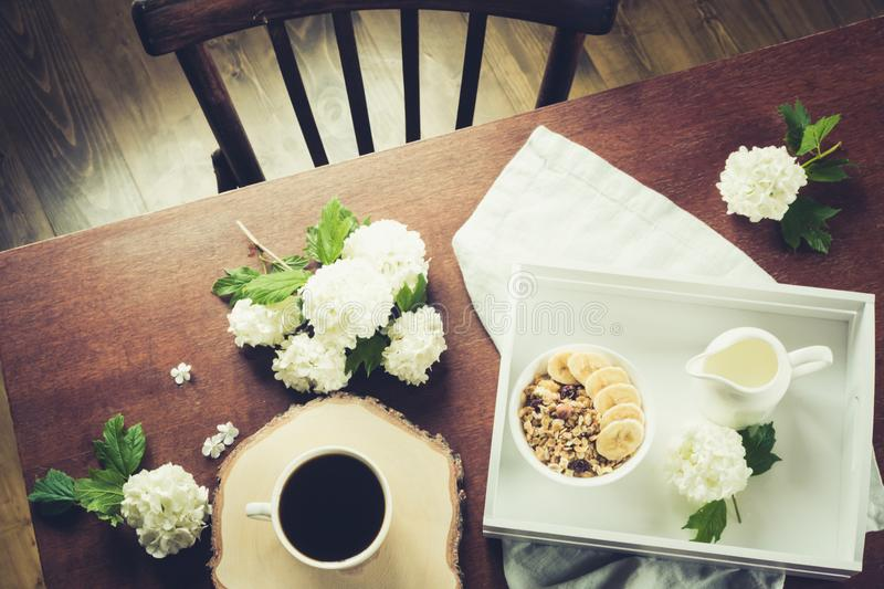 Healthy breakfast. Cup of coffee, homemade oatmeal granola and nuts, decor flowers of viburnum in interior. View from above. Healthy breakfast. Cup of black royalty free stock photos