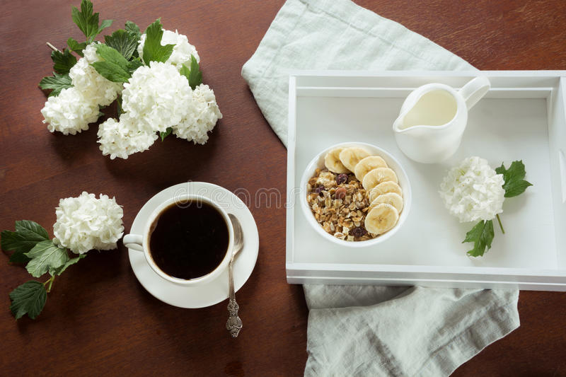 A healthy breakfast is a cup of coffee with muesli, sliced bananas and decor with flowers of viburnum. View from above. royalty free stock image