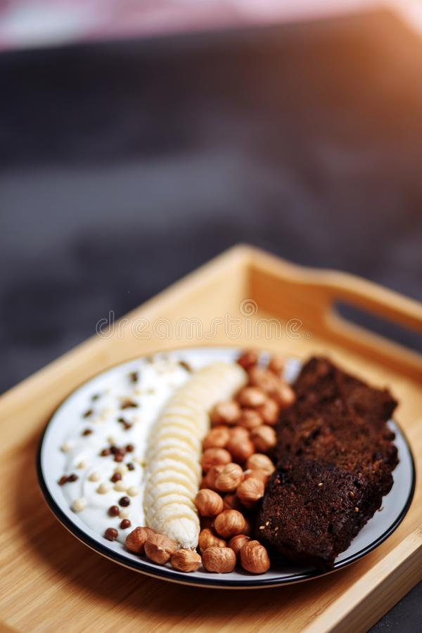 Healthy breakfast with delicious bread, banana, hazelnut and yogurt in bowl stock photos
