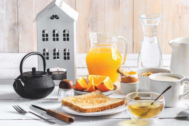 Healthy breakfast eating concept, various morning food - pancakes, soft-boiled egg, toast, oatmeal, granola, fruit, coffee, tea,. Orange juice milk on white stock photo
