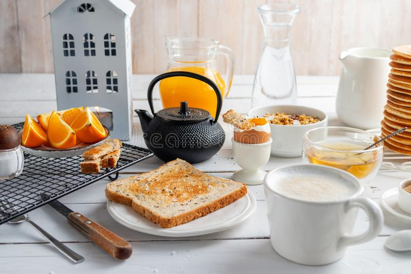 Healthy breakfast eating concept, various morning food - pancakes, soft-boiled egg, toast, oatmeal, granola, fruit, coffee, tea, stock photo