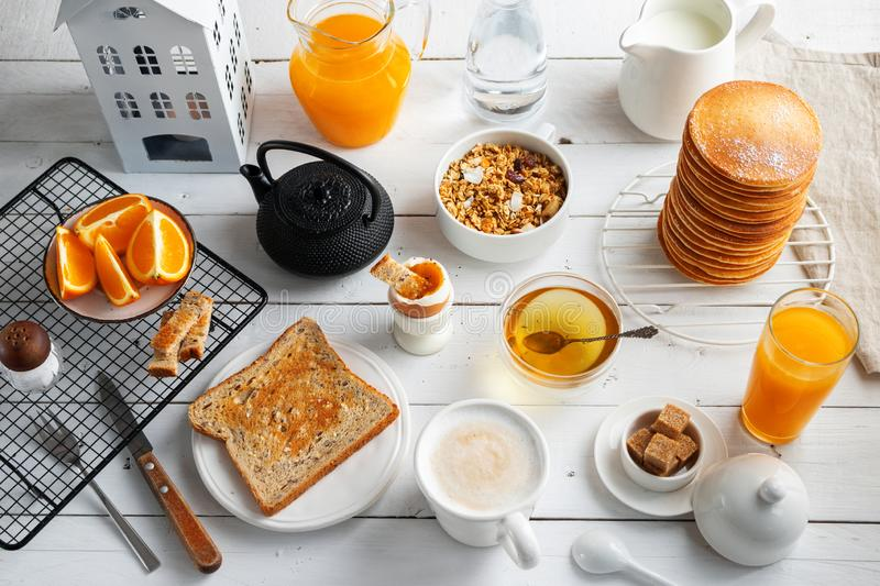 Healthy breakfast eating concept, various morning food - pancakes, soft-boiled egg, toast, oatmeal, granola, fruit, coffee, tea, royalty free stock photos