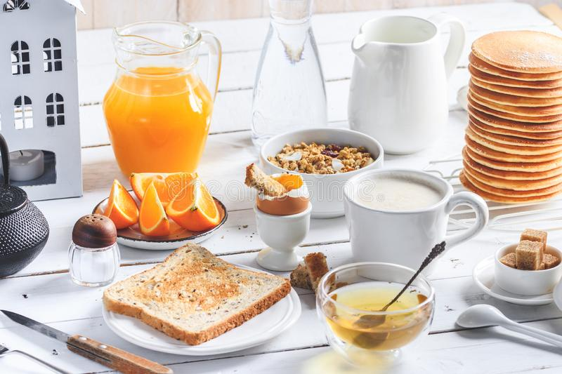 Healthy breakfast eating concept, various morning food - pancakes, soft-boiled egg, toast, oatmeal, granola, fruit, coffee, tea, royalty free stock photography