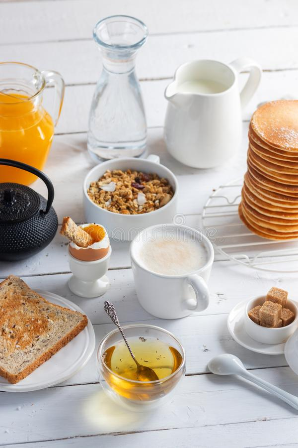 Healthy breakfast eating concept, various morning food - pancakes, soft-boiled egg, toast, oatmeal, granola, fruit royalty free stock photo
