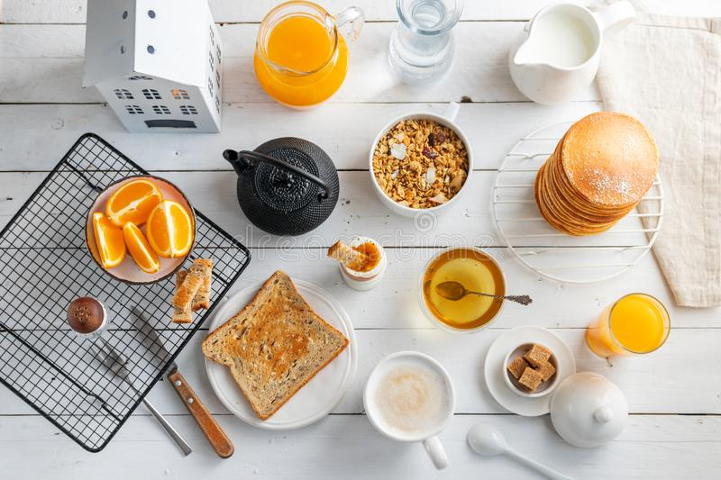 Healthy breakfast eating concept, various morning food - pancakes, soft-boiled egg, toast, oatmeal, granola, fruit royalty free stock image