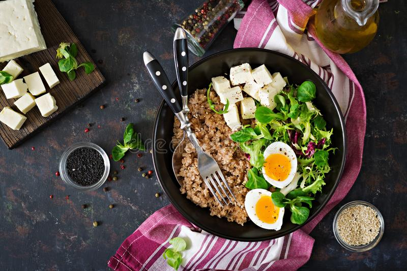 Healthy breakfast with egg, cheese, lettuce and buckwheat porridge on dark background. Proper nutrition. Dietary menu. Flat lay. Top view royalty free stock photos