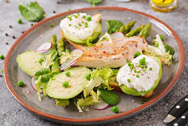 Eggs poached on toast with avocado, asparagus and chicken fillet on grill. stock images