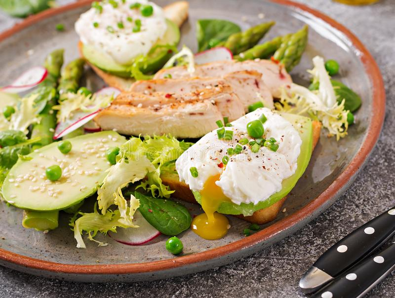 Eggs poached on toast with avocado, asparagus and chicken fillet on grill. stock image