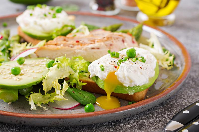 Eggs poached on toast with avocado, asparagus and chicken fillet on grill. stock photos