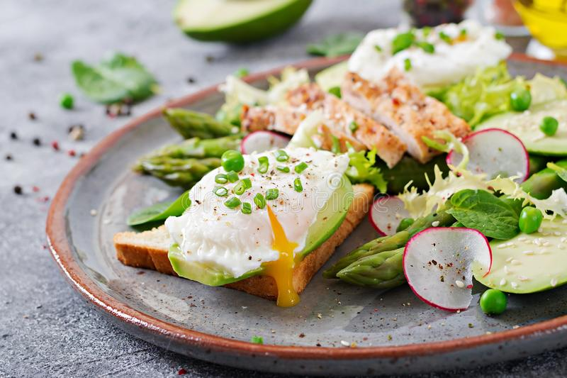 Eggs poached on toast with avocado, asparagus and chicken fillet on grill. royalty free stock image