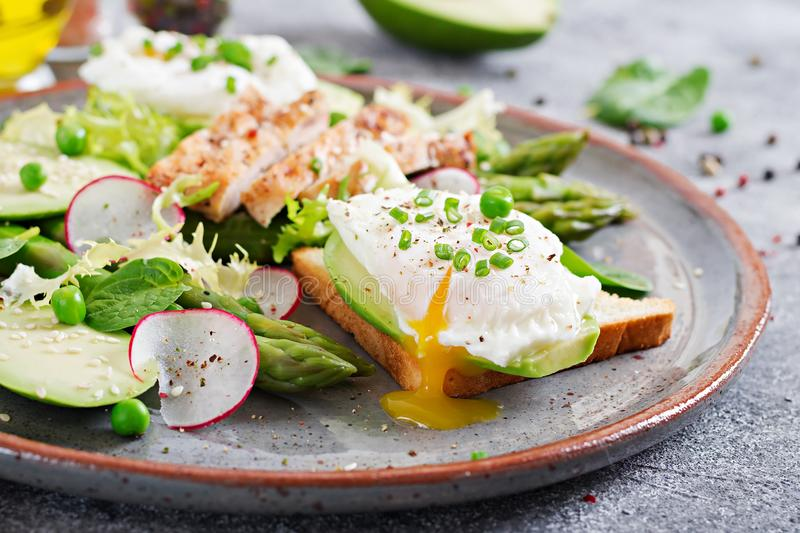 Eggs poached on toast with avocado, asparagus and chicken fillet on grill. stock photography