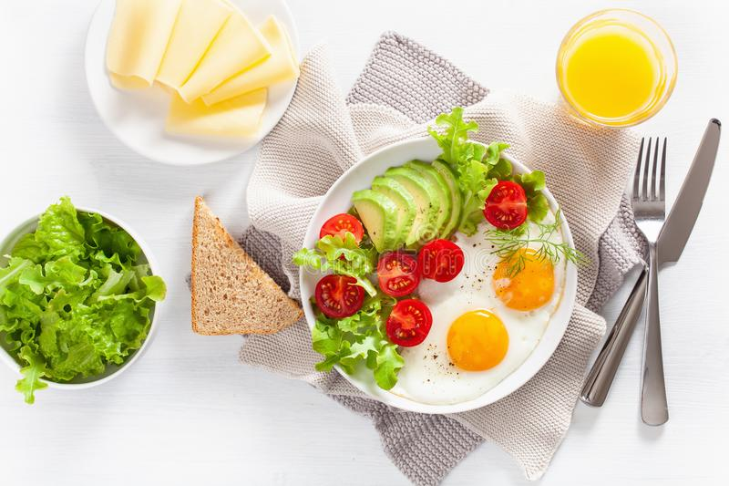 Healthy breakfast flat lay. fried eggs, avocado, tomato, toasts. And coffee stock image