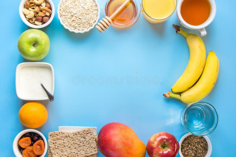 Healthy Breakfast Food Fiber Source Oatmeal Honey Fruits Apples Banana Orange Juice Water Green Tea Nuts. Blue Tabletop. Modern Funky Flat Lay Frame Vivid royalty free stock photography