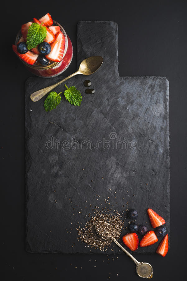 Healthy breakfast food frame. Chia pudding with fresh berries and mint on black slate stone board over dark background royalty free stock images