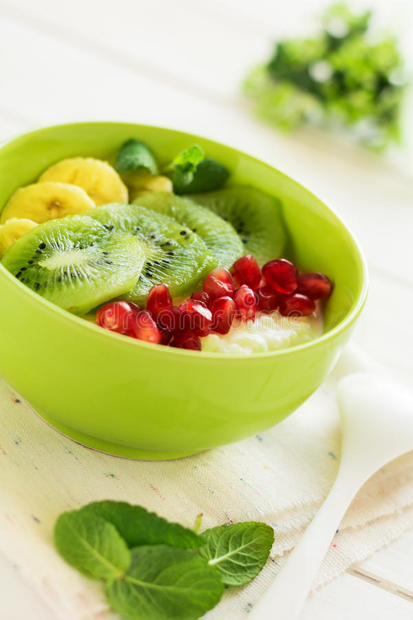 Healthy breakfast: fresh cottage cheese with kiwi, banana, garnet seeds and honey decorated mint leaves. On white wooden table. Selective focus stock image
