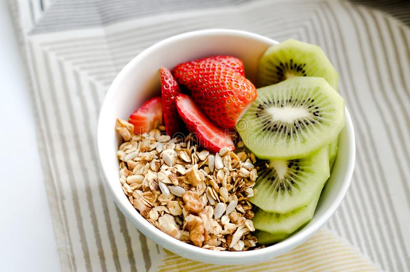 Healthy breakfast fresh granola, muesli in bowl with cereal, nuts, banana fruit, honey with drizzlier, glass of water royalty free stock photography