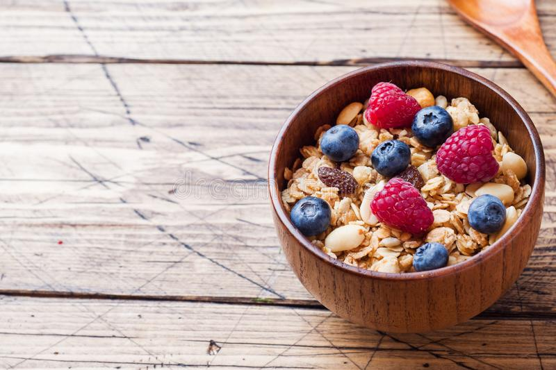 Healthy breakfast. Fresh granola, muesli with yogurt and berries on wooden background. Copy space royalty free stock image