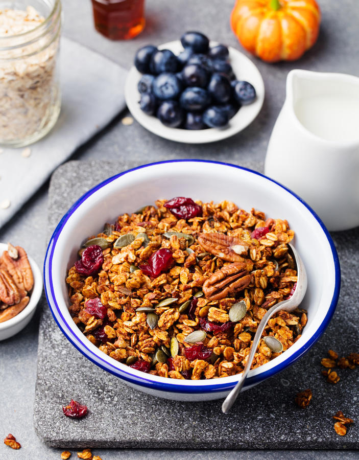 Healthy breakfast. Fresh pumpkin granola, muesli with seeds, pecan nuts, cranberries and maple syrup. In white bowl stock photos