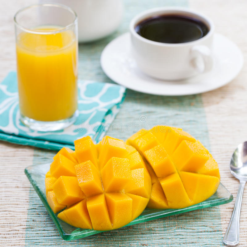 Healthy breakfast Fresh tropical fruit mango and orange juice, coffee royalty free stock images