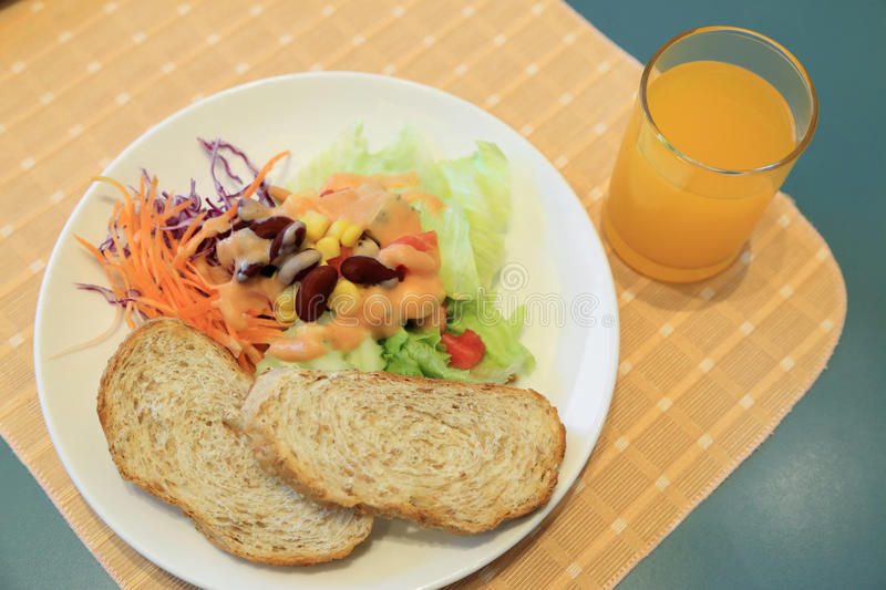 Healthy breakfast, Fresh vegetable salad with toast and orange juice royalty free stock photography
