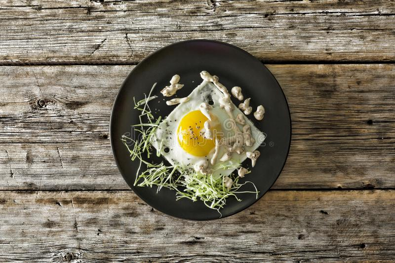 Healthy breakfast. Fried egg on a black plate with micro-green and quinoa. Top view, closeup. royalty free stock image
