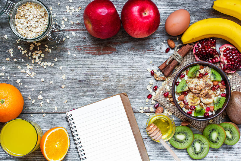 Healthy breakfast with fruit oatmeal and recipe book stock photos