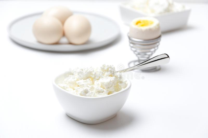 Healthy breakfast full of protein and calcium.Cottage cheese, eggs.White and bright colors. Delicious cottage cheese, eggs for lunch.Concept of healthy eating stock images