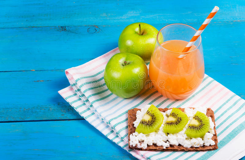 Healthy breakfast. A glass of freshly squeezed grapefruit juice, green apple and toast with cheese and kiwi slices. Copy space stock image
