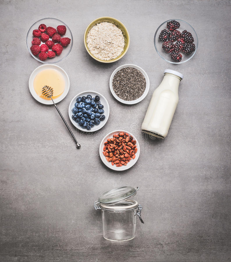 Healthy breakfast glass jar making with ingredients: chia seeds, goji berries, oatmeal , fresh berries , honey and milk or yogurt. Top view, copy space royalty free stock photography