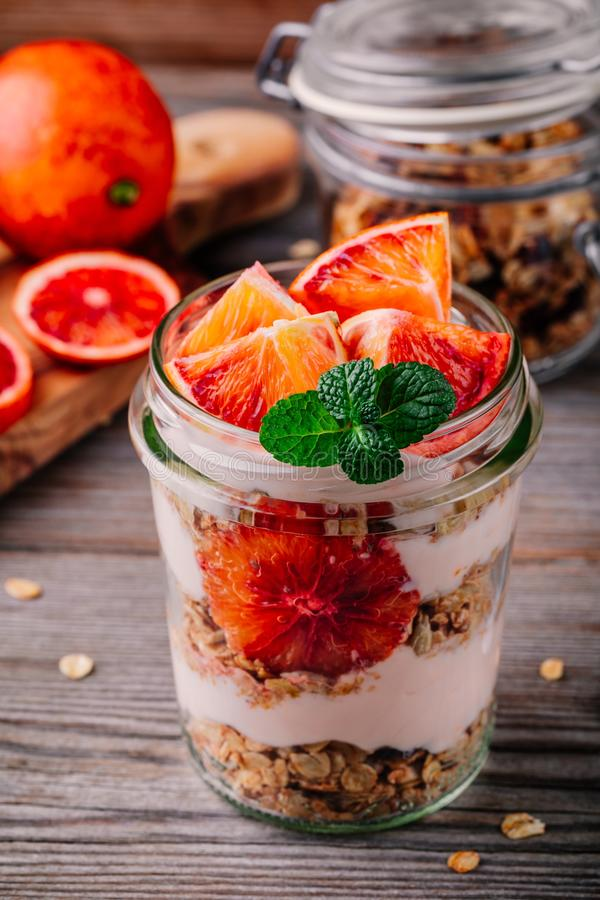 Healthy breakfast glass jar yoghurt parfait with homemade granola and blood orange on a wooden background. Healthy breakfast in a glass jar. yoghurt parfait with stock image