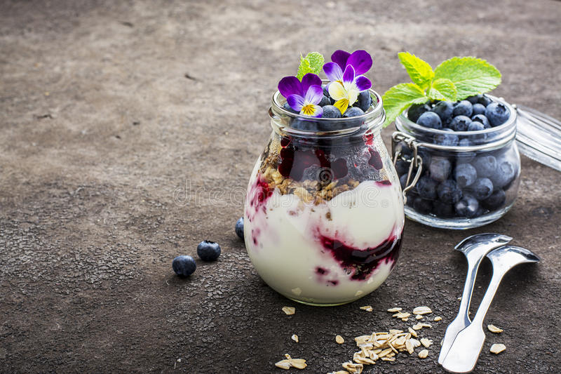 Healthy breakfast in a glass jar: yogurt, berry puree, whole grain cereal cereal, edible flowers, blueberries on a dark. Background. The concept of proper stock image