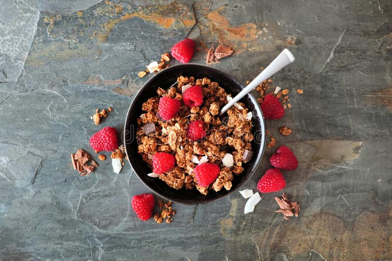 Healthy breakfast granola with dark chocolate, raspberries and coconut, top view. Healthy breakfast granola topped with dark chocolate, raspberries and coconut stock photo