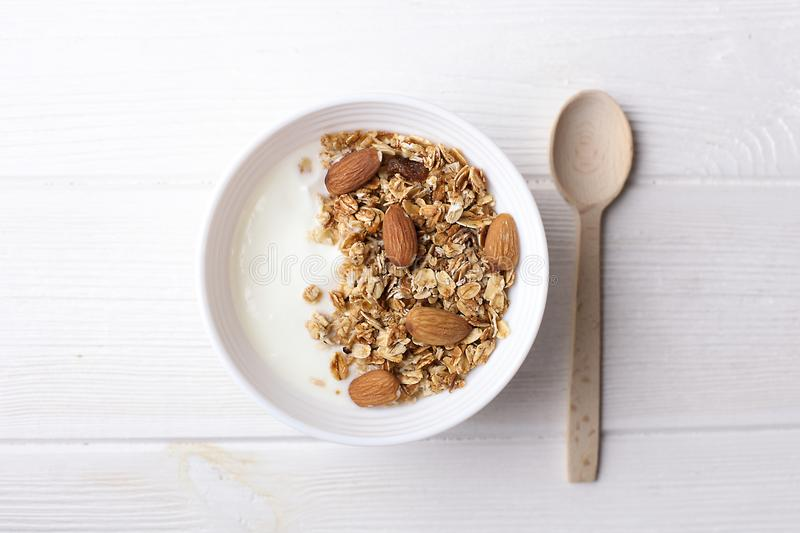 Healthy breakfast granola with greek yogurt, honey, mix nuts on white wooden background top view, copy space royalty free stock images