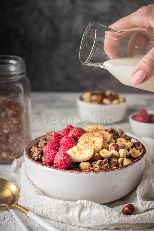 Healthy breakfast granola in a plate with nuts, banana and raspberries, milk is poured from a bottle royalty free stock photos