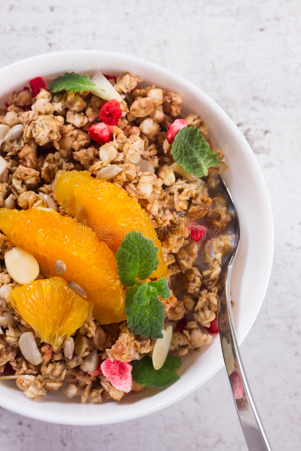 Healthy breakfast with granola. Healthy breakfast - plate of granola with orange slices, mint and seeds close up stock images