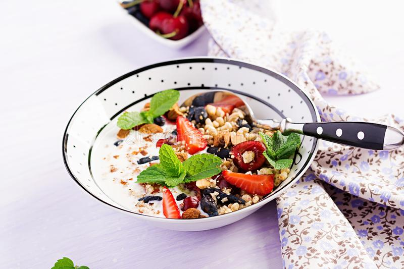 Healthy breakfast - granola, strawberries, cherry, honeysuckle berry, nuts and yogurt in a bowl. Vegetarian concept food royalty free stock photo